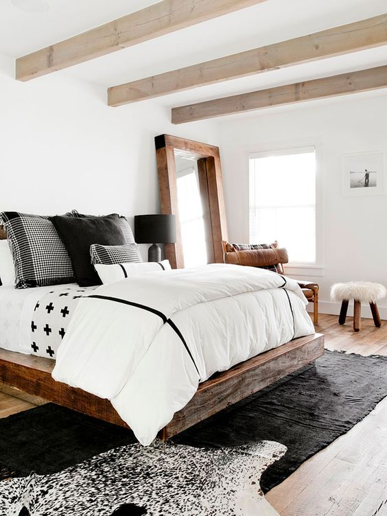 a modern farmhouse bedroom with light-stained wooden beams, a rich-stained wooden bed, black and white bedding and layered rugs
