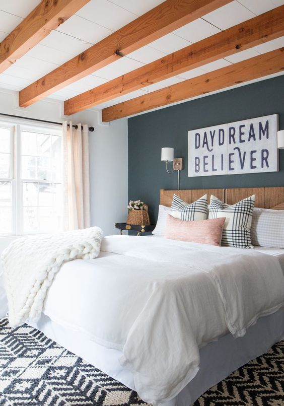 a modern farmhouse bedroom with rich-stained wooden beams on the ceiling, a stained bed, neutral bedding, a black accent wall and a printed rug