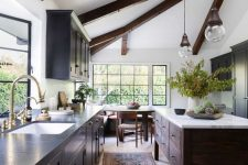 a modern farmhouse kitchen with navy cabinets, a dark stained kitchen island, dark stained beams and vintage lamps