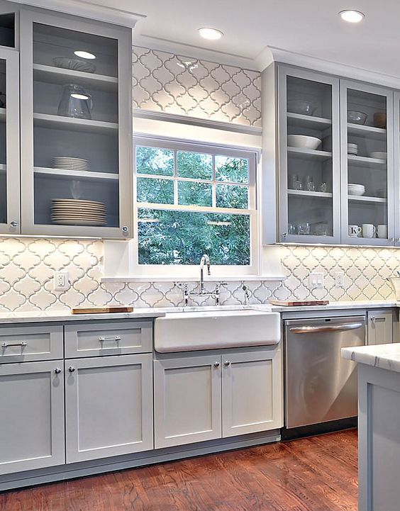 a modern light grey kitchen with shaker cabinets and glass ones, with a white wall clad with white arabesque tiles and white stone countertops