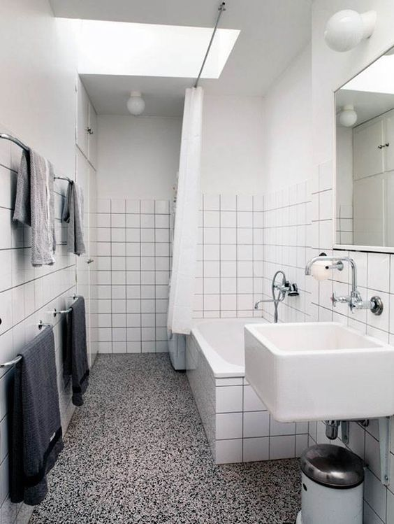 a modern monochromatic bathroom with white square tiles, a terrazzo floor, a floating sink, black and grey towels and a skylight