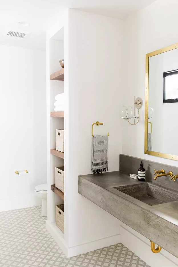 a modern neutral bathroom with built-in shelves, a built-in concrete sink, gold fixtures and a tiled floor is cool