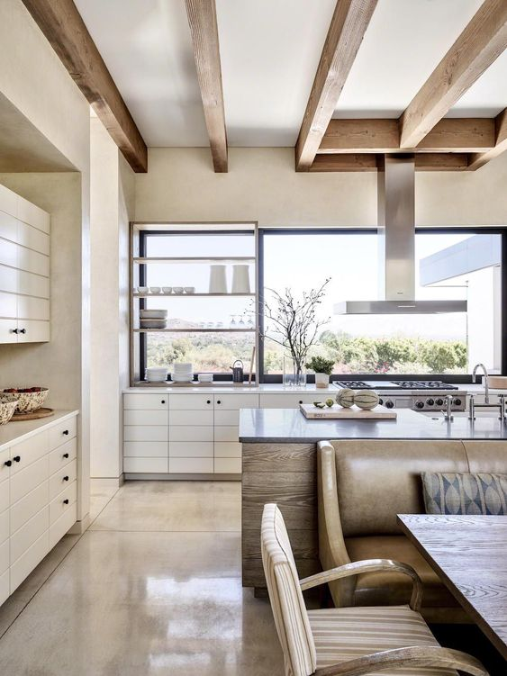 a modern neutral open layout with wooden beams, sleek white kitchen and a dining zone with a leather sofa and striped chairs