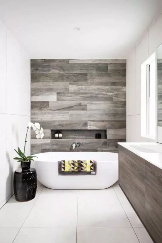 a modern refined bathroom clad with neutral and wood look tiles, with a niche, an oval tub, a wooden vanity and potted blooms