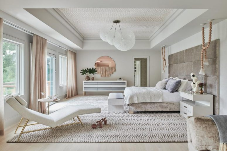 a modern refined bedroom in neutrals, with anupholstered bed, neutral bedding, a cool dresser, a creamy lounger, blush curtains and a copper mirror