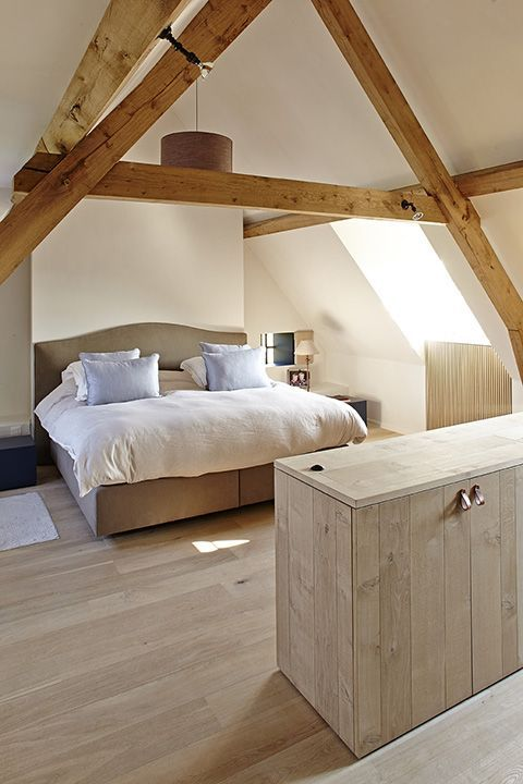 a modern rustic attci bedroom with wooden beams, a neutral upholstered bed, neutral bedding and nneutral planked furniture