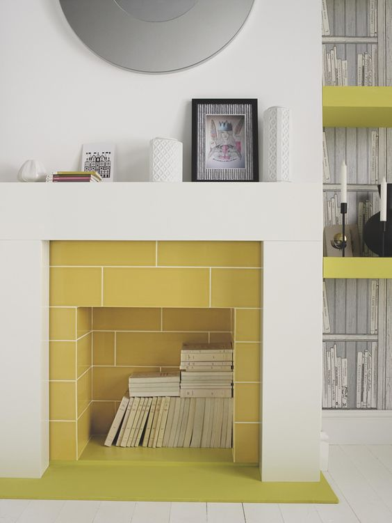 a modern sleek fireplace clad with yellow tiles, with books stored inside is a real centerpiece in a modern living room