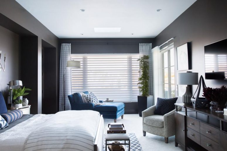 a modern taupe bedroom with a bed in the niche, a blue lounger, a grey chair, potted plants and printed textiles
