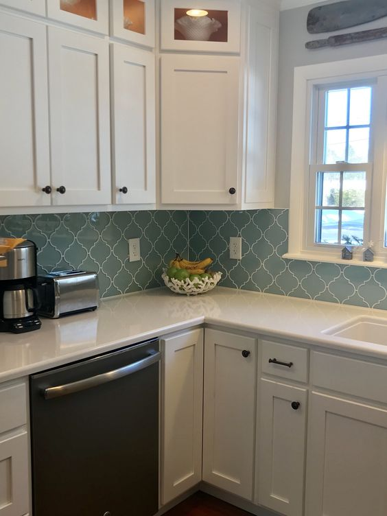a modern white kitchen with black knobs and a blue arabesque tile backsplash plus white grout that accents the tiles
