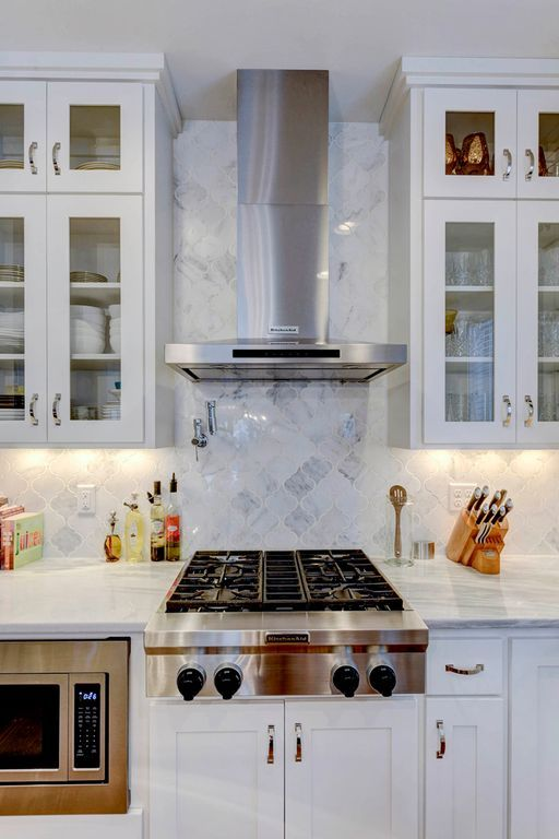 a modern white kitchen with upper glass cabinets, with a white marble arabesque tile backsplash and built-in appliances is amazing