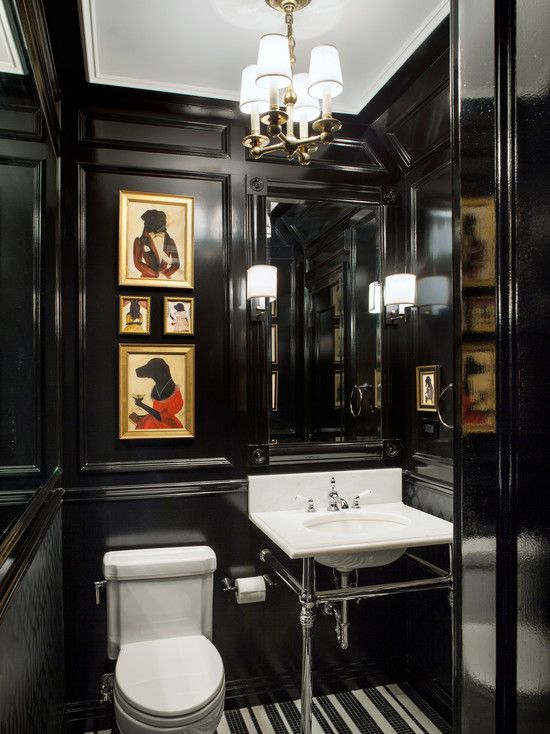 a moody and elegant powder room with black paneling, a built-in mirror, a console sink, a white toilet and a mini gallery wall in bold colors
