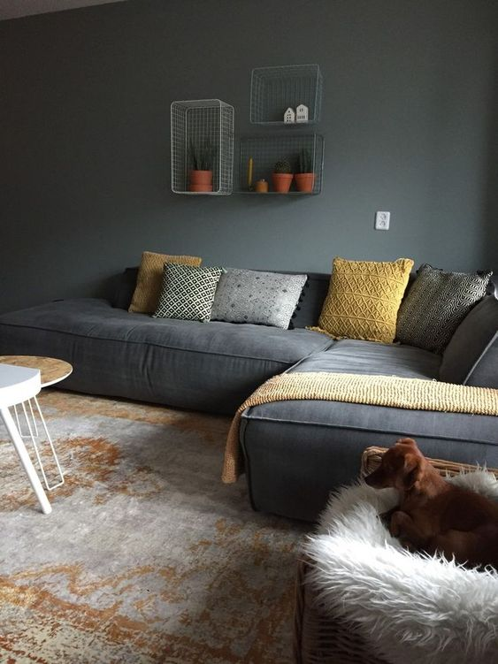 a moody living room with grey walls, a grey low sofa, grey and yellow pillows, a woven chair with faux fur and wire box shelves