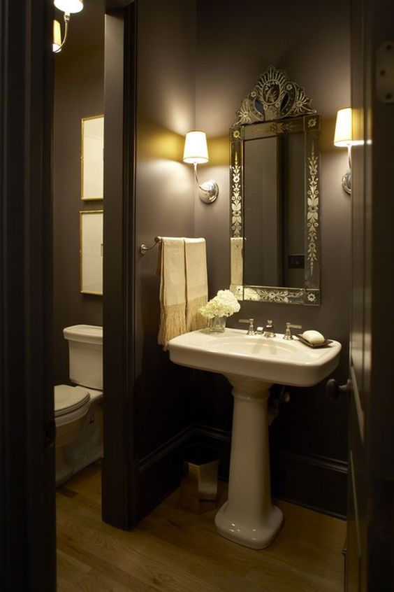 a moody powder room with black walls, a pedestal sink, a mirror in an ornated frame, a towel holder and sconces is a very chic idea