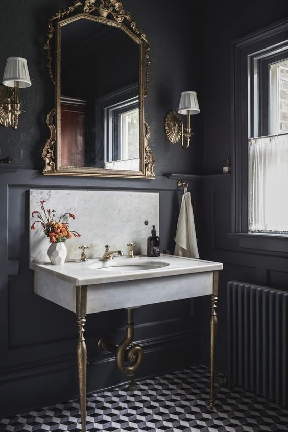 a moody powder room with black walls and paneling, a console sink, a mirror in an ornated frame, sconces and neutral textiles