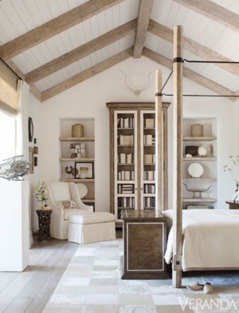 a neutral French farmhouse bedroom with wooden beams, a stained bookcase, built-in shelves, a cnaopy bed and a neutral chair