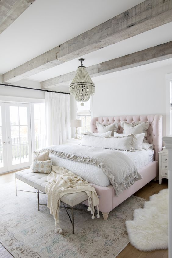 a neutral and chic French farmhouse bedroom with whitewashed wooden beams, a pink upholstered bed, neutral bedding and a soft bench, a wooden bead chandelier