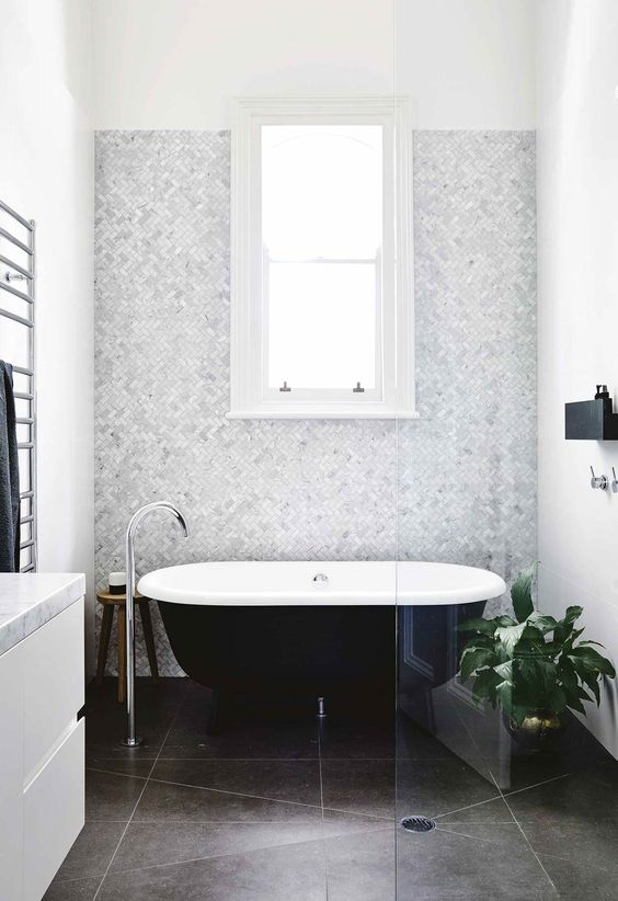 a neutral and chic bathroom with a grey marble accent wall, dark tiles on the floor, a black clawfoot tub, a white vanity and a black mini shelf