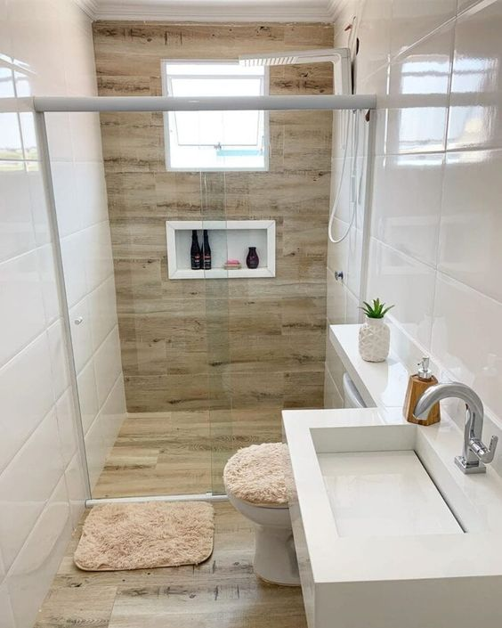 a neutral and pretty bathroom clad with white tiles, with light wood look tiles in the shower and on the floor, with a niche, white appliances and a small window