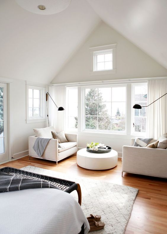 a neutral attic farmhouse bedroom with a black woven bench, creamy chairs by the window and a round ottoman plus black sconces