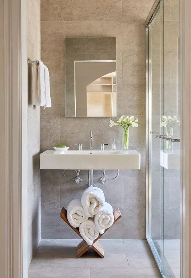 a neutral bathroom with a floating sink, a stand with towels, a mirror with no frame and a shower space enclosed in glass