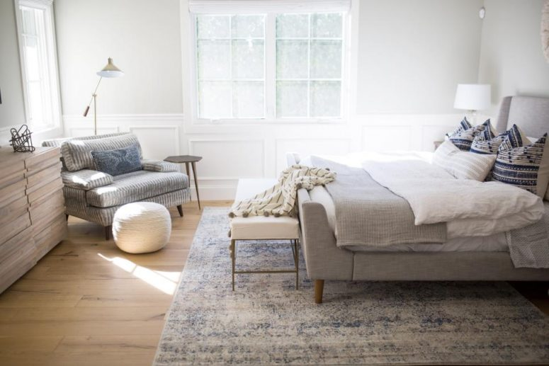 a neutral bedroom with a grey upholstered bed, neutral bedding, a creamy bench, a striped chair, a stained dresser is cool