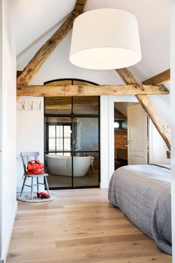 a neutral bedroom with light-stained wooden beams, a bed with neutral bedding, a pendant lamp and a grey chair plus a window to the bathroom