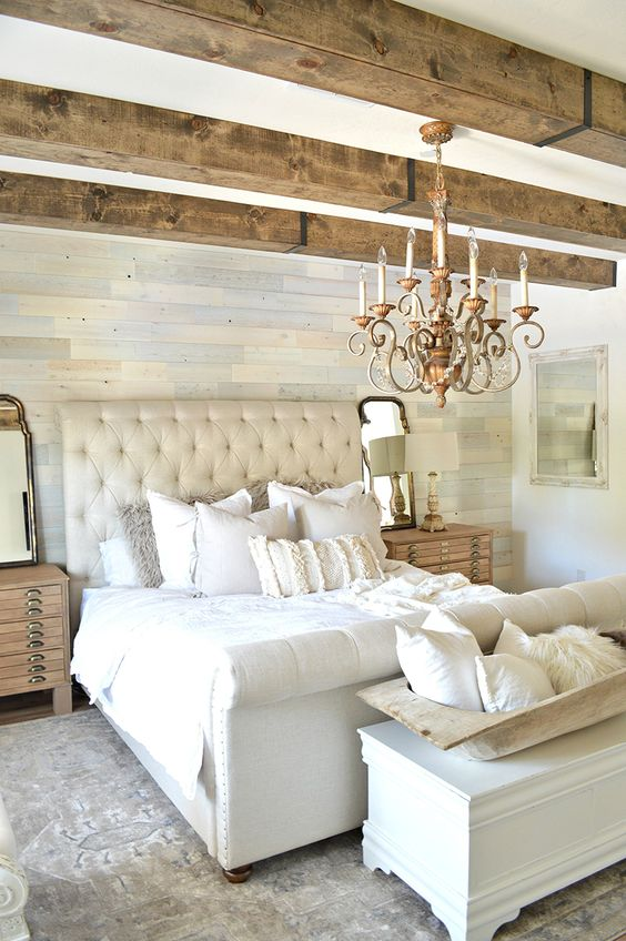 a neutral farmhouse bedroom with a catchy wallpaper accent wall, wooden beams, neutral furniture and stained nightstands plus a refined chandelier