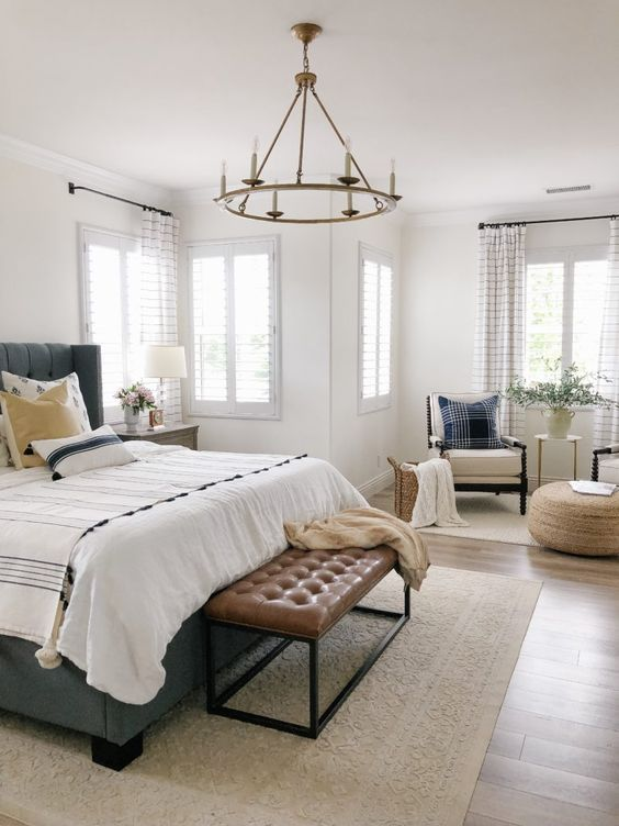 a neutral farmhouse bedroom with a grey bed, a brown leather bench, neutral chairs, a jute pouf and a chandelier