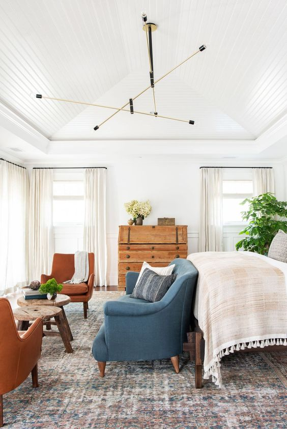 a neutral farmhouse bedroom with a large bed, a blue loveseat, rust chairs, wooden stools and a dresser, potted plants and neutral textiles