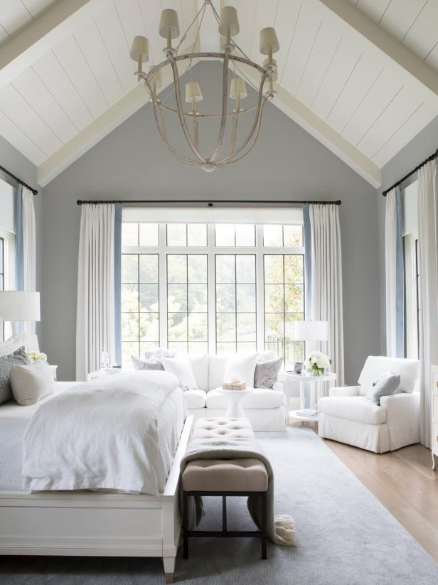a neutral farmhouse bedroom with a white bed, a sofa, chairs, a creamy upholstered bench, a chandelier and neutral textiles