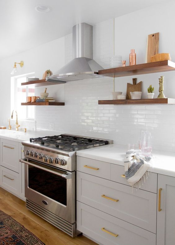 a neutral farmhouse kitchen with a whiye skinny tile backsplash, countertops and thick floating shelves and gold touches