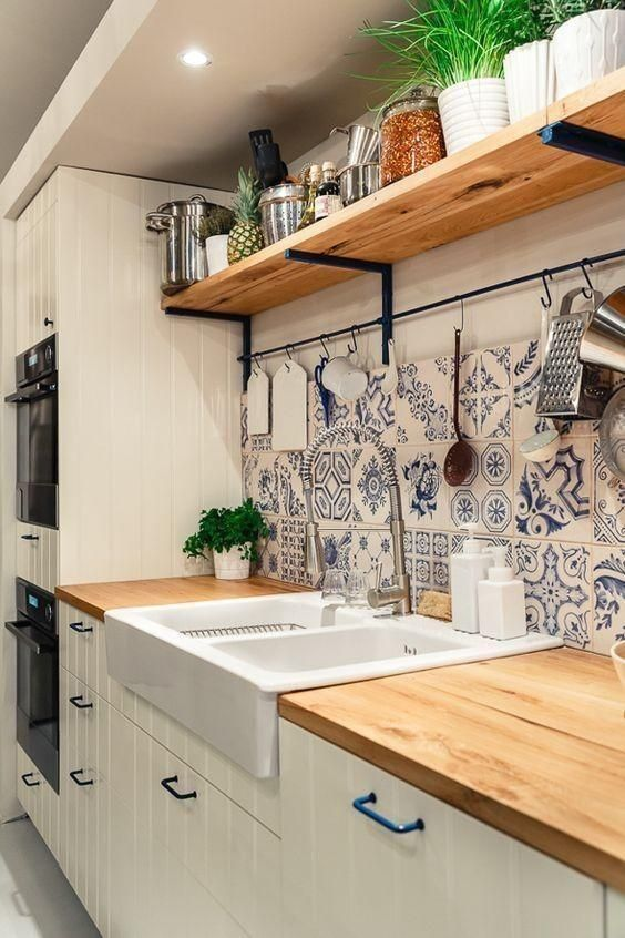 a neutral farmhouse kitchen with planked cabinets, butcherblock countertops, blue Mrooccan tiles on the backsplash and an open shelf