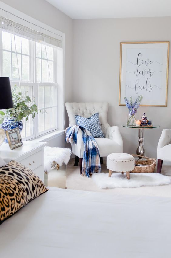 a neutral glam bedroom with a bed, white nightstands, creamy chairs, a round coffee table, bright printed textiles and pretty blooms