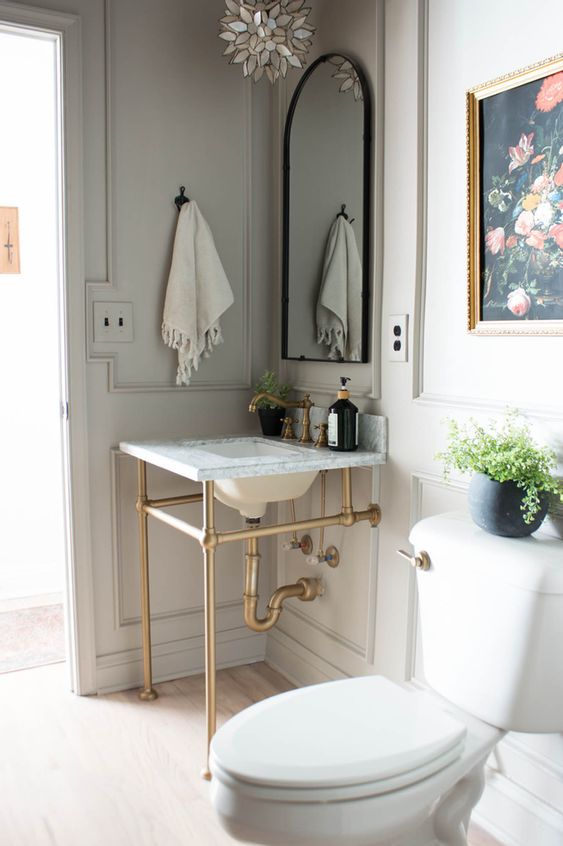 a neutral vintage powder room with grey paneled walls, a console sink, an arched mirror, white appliances and a pretty artwork