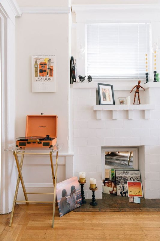 a non-working white brick fireplace used to display vinyl and posters is a lovely idea and it looks very chic and pretty