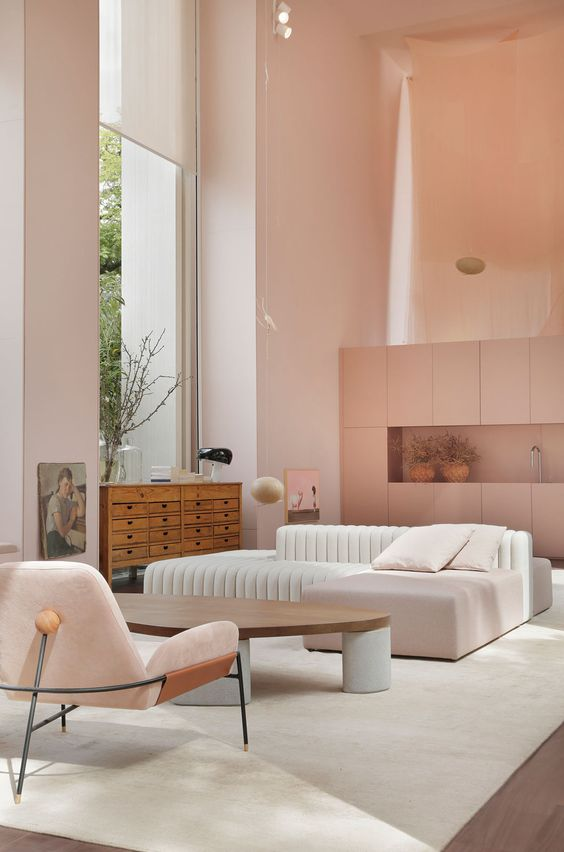 a pink minimalist living room with a white low sofa, a pink chair, a low coffee table and a wooden sideboard