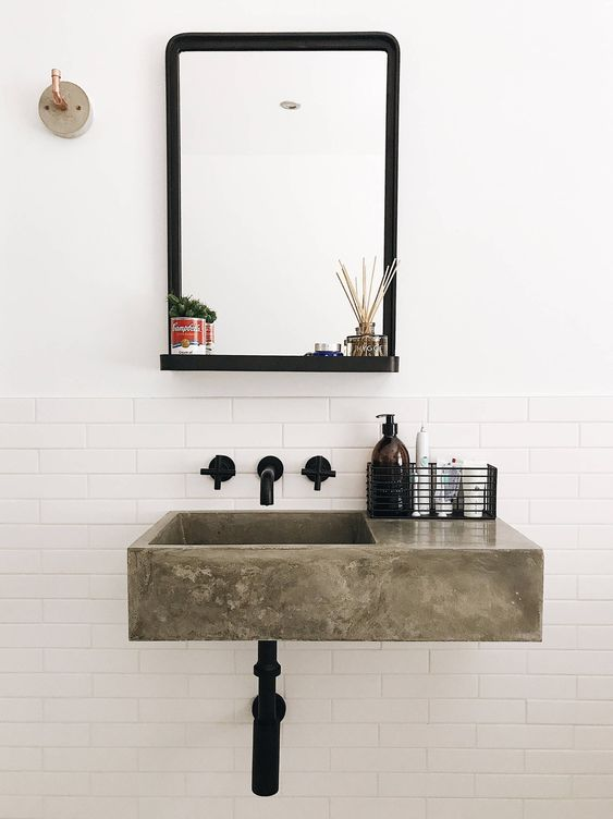 a polished concrete floating sink, black fixtures and a mirror in a black frame for a chic and beautiful bathroom look in modern style