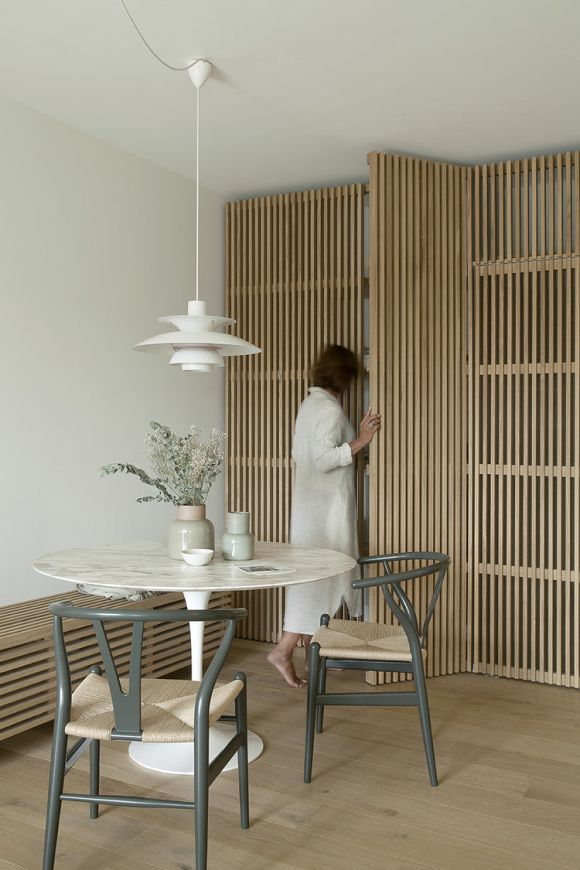 a pretty Japandi nook with a storage space done with wooden slab doors, with a round table and woven chairs plus a pendant lamp