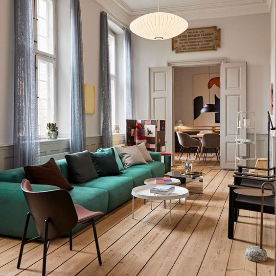 a pretty and bright living room with a green low sofa, dark chairs, round tables and colored pillows plus blue curtains
