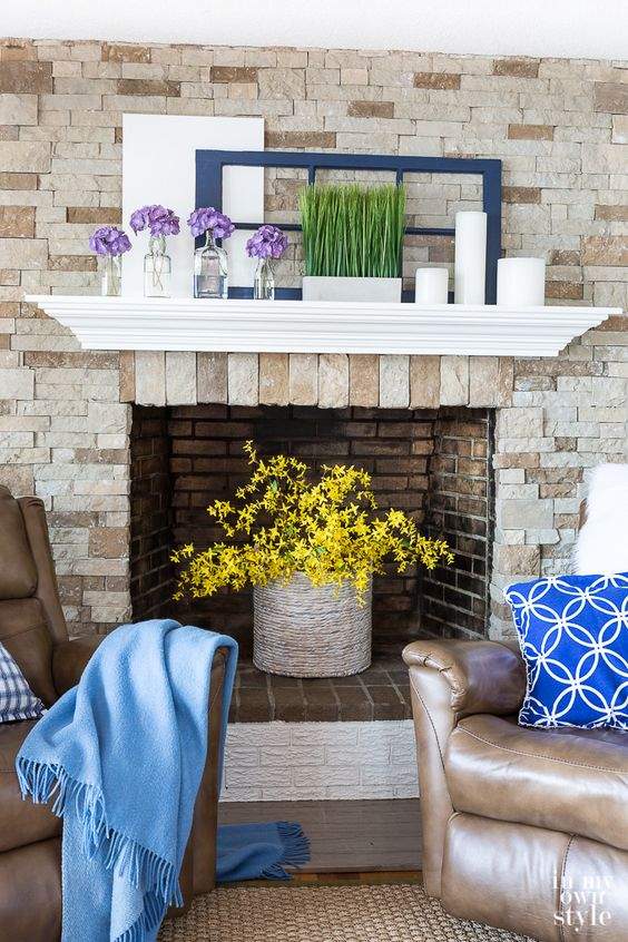 a pretty and bright space with colorful blooms in a basket, some grass, flowers and candles and bright textiles is cool