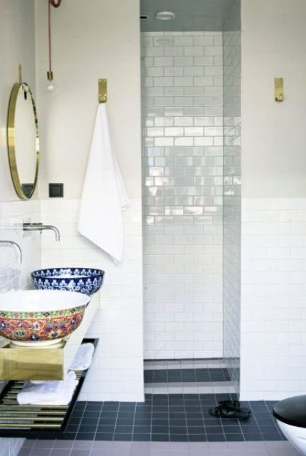 a pretty bathroom clad with white subway tiles and black square ones, a gilded floating vanity, patterned Moroccan vessel sinks and mirrors in gilded frames
