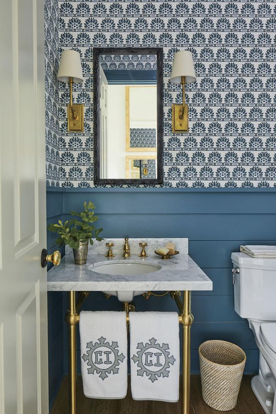 a pretty bright powder room with blue wallpaper and blue planks on the walls, a console sink, elegant sconces and a basket for trash
