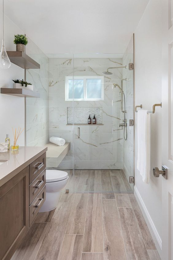 a pretty contemporary bathroom clad with white stone tiles and wood look ones on the floor, a wooden vanity, open shelves and cool brass fixtures