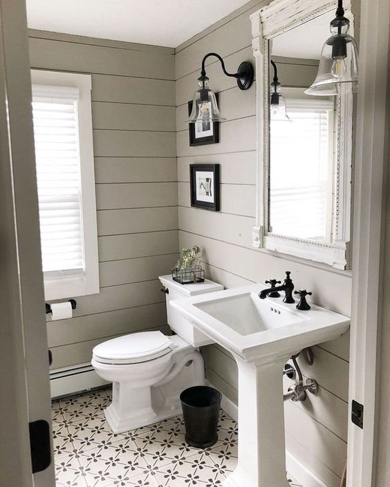 a pretty farmhouse bathroom with planked walls, a pedestal sink, a small gallery wall, vintage sconces and black touches for a contrasting look
