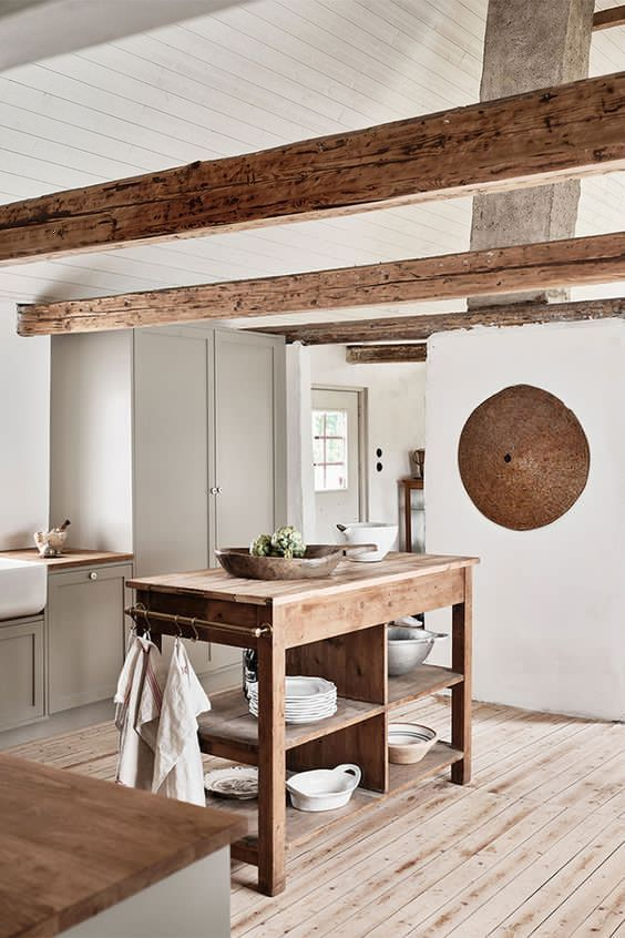 a pretty grey kitchen with shaker cabinets, wooden beams, butcherblock countertops and a stained kitchen island is cool