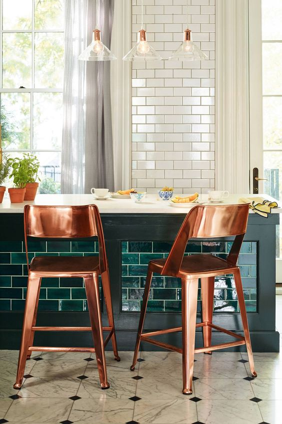 a pretty kitchen with white tiles and a kitchen island clad with emerald tiles, with chic copper stools and pendant lamps is wow
