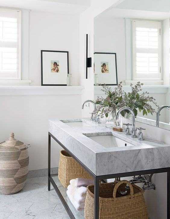 a pretty neutral farmhouse bathroom with chevron tiles, a double console sink, some baskets for storage and an oversized mirror
