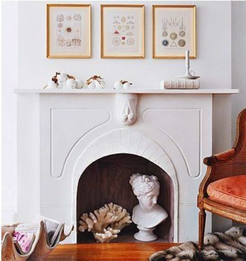 a pretty non-working fireplace with a gallery wall over the mantel, candles, white pumpkins, a coral and a statue inside the fireplace