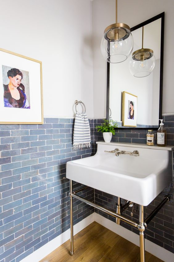 a pretty powder room with blue tiles on the walls, a console sink, a mirror in a black frame and a pendant lamp plus a bold artwork