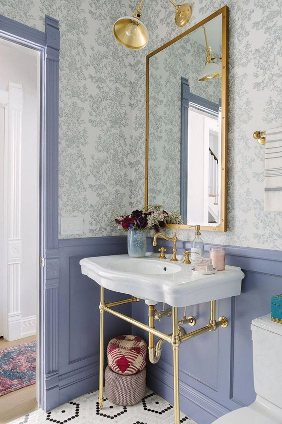 a pretty powder room with floral wallpaper, blue panels, a console sink, a mirror in a gilded frame, sconces and white appliances